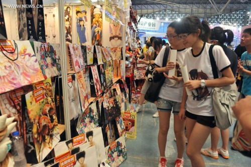 Visitors select comics products during the 9th China International Comics Games Expo (CCG Expo) in Shanghai, east China, July 11, 2013. A total of 325 animation and game companies from home and abroad took part in the five-day expo, which kicked off here on Thursday. [Photo: Xinhua/Liu Xiaojing]