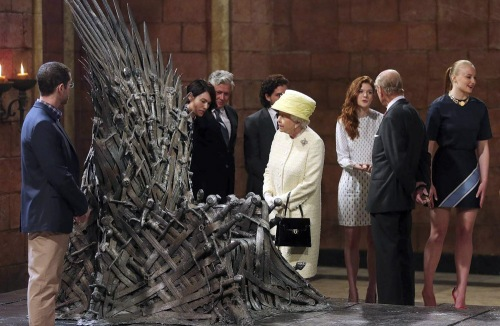 While Queen Elizabeth examines the Iron Throne, Prince Philip greets Thrones cast members (from right) Sophie Turner (Sansa), Rose Leslie (Ygritte), Kit Harington (Jon Snow), Conleth Hill (Varys), and Lena Headey (Cersei). To the left of the Throne is series co-creator D.B. Weiss.(REUTERS/Jonathan Porter/Pool)