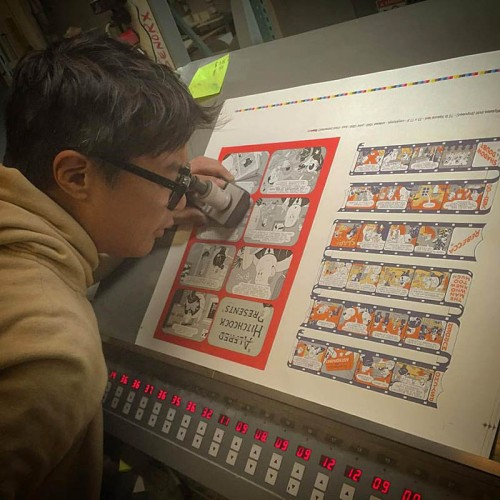 Alvin Buenaventura examining proofs of an upcoming oversized comics project from Pigeon Press